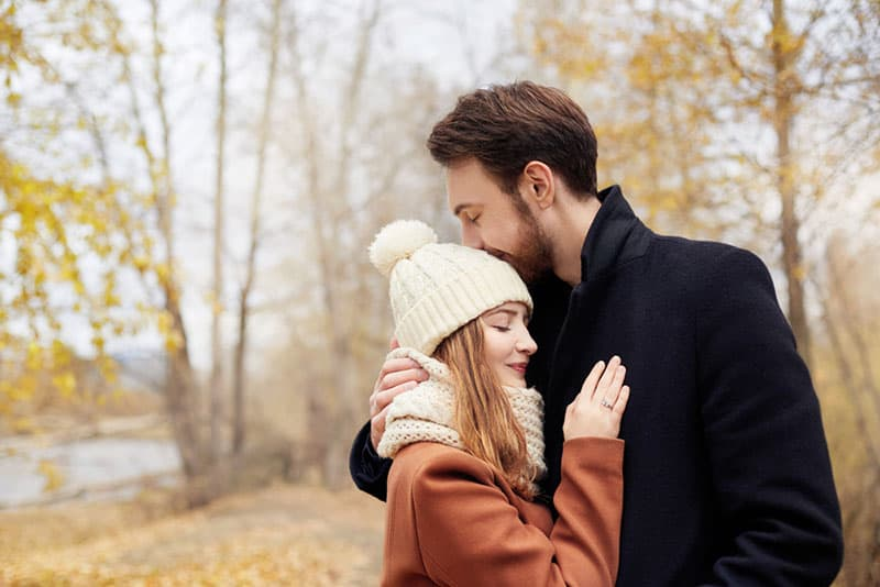man kissing a woman in the hat