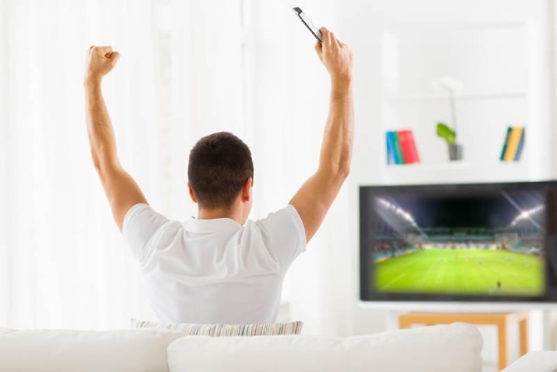 man watching football game on tv