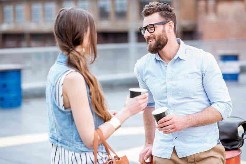 man wearing white shirt talking to woman