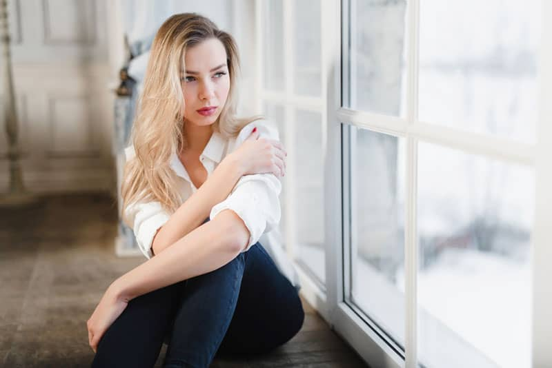 mindful blond woman sitting by the window