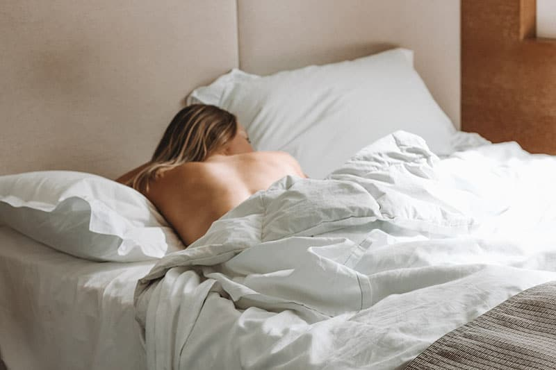 naked woman sleeping in bed