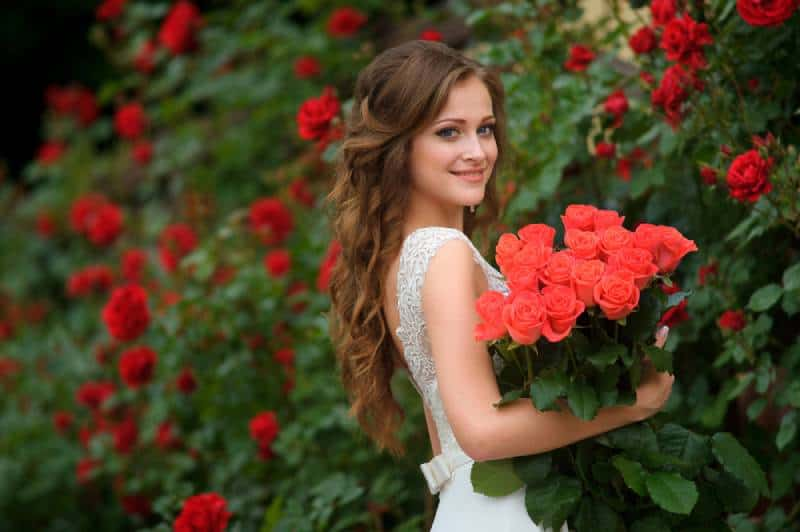 pretty girl with long hair and white dress holding bucket red roses
