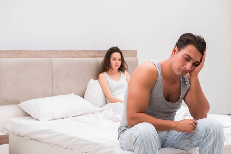 sad couple sitting on bed in bedroom