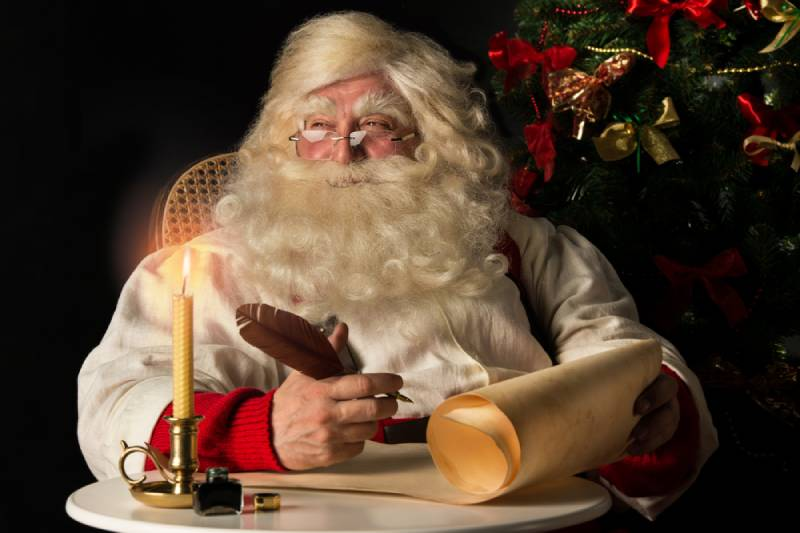 santa claus sitting at home and writing on old paper roll