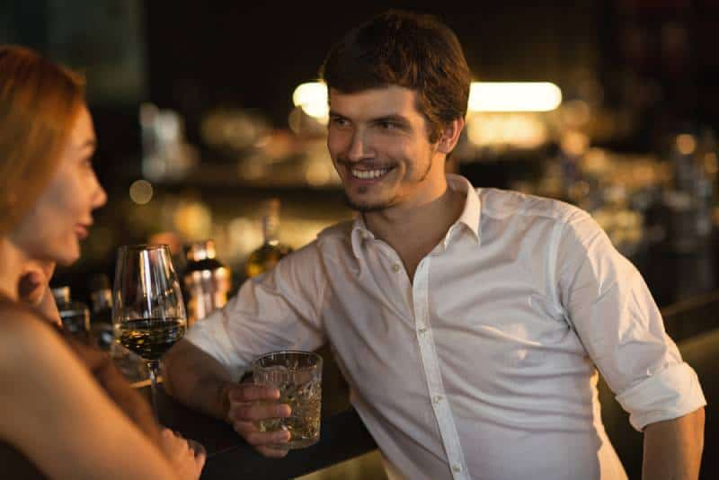 seductively woman at the bar with smiling man