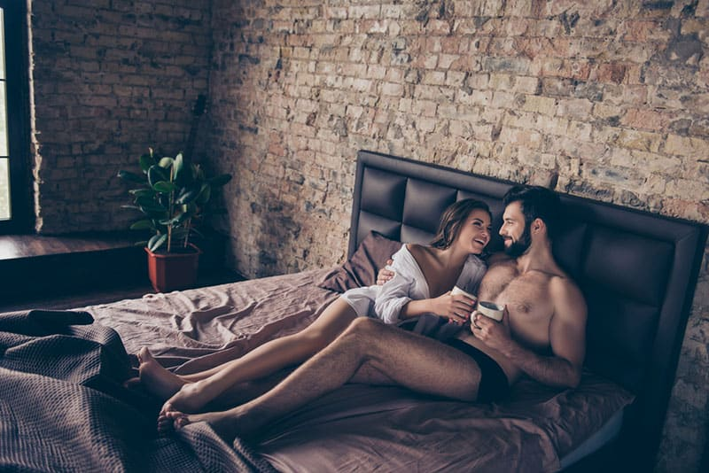 sexy couple talking and drinking coffee in bed