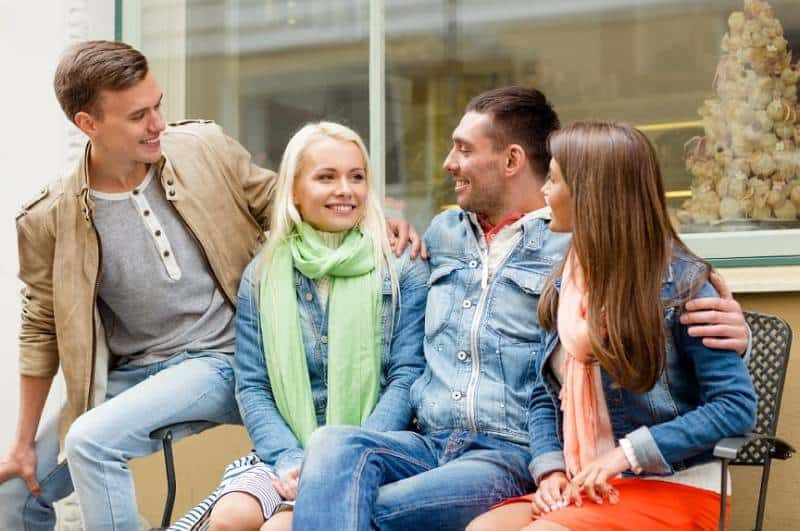 smiling group of friends sitting on a park bench