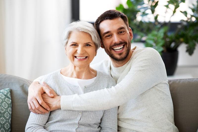 smiling man hugging his mother