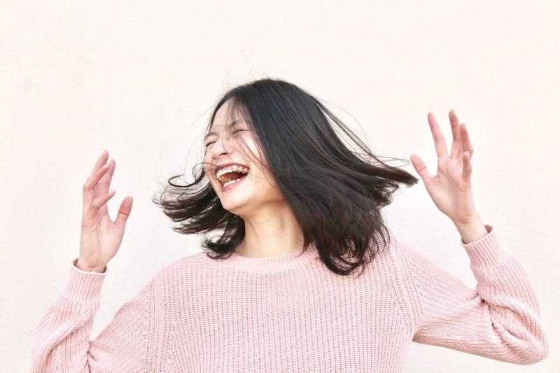 smiling woman wearing pink sweater