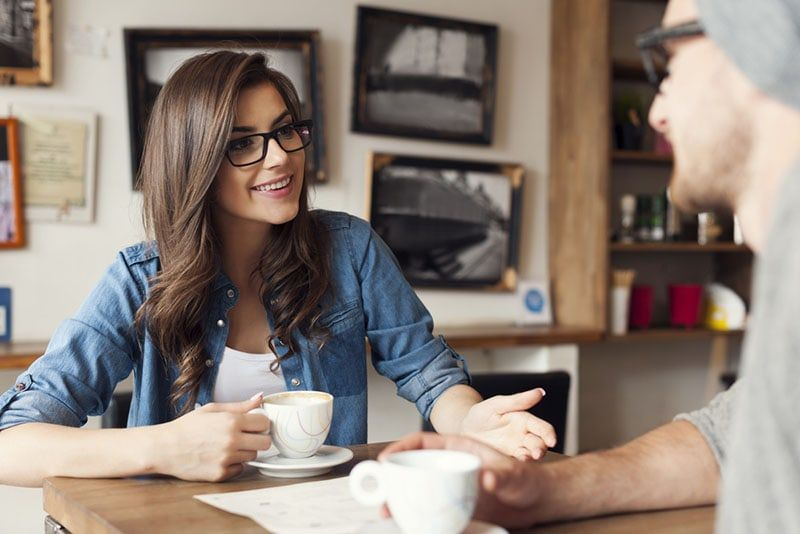 smiling woman with glasses talking to man at cafe