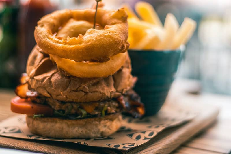 tasty burger with onion rings served on plate