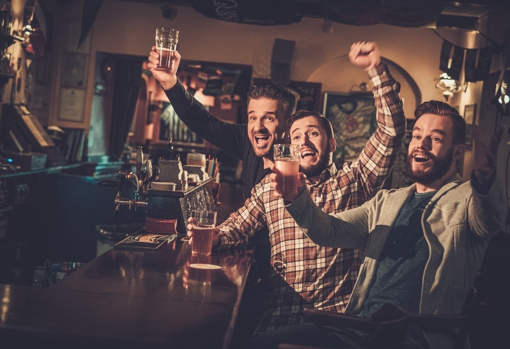 three friends at the bar drinking beers and watching a match