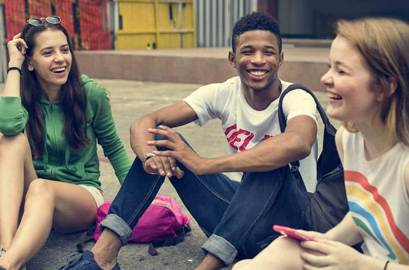 three smiling tenagers sitting outside