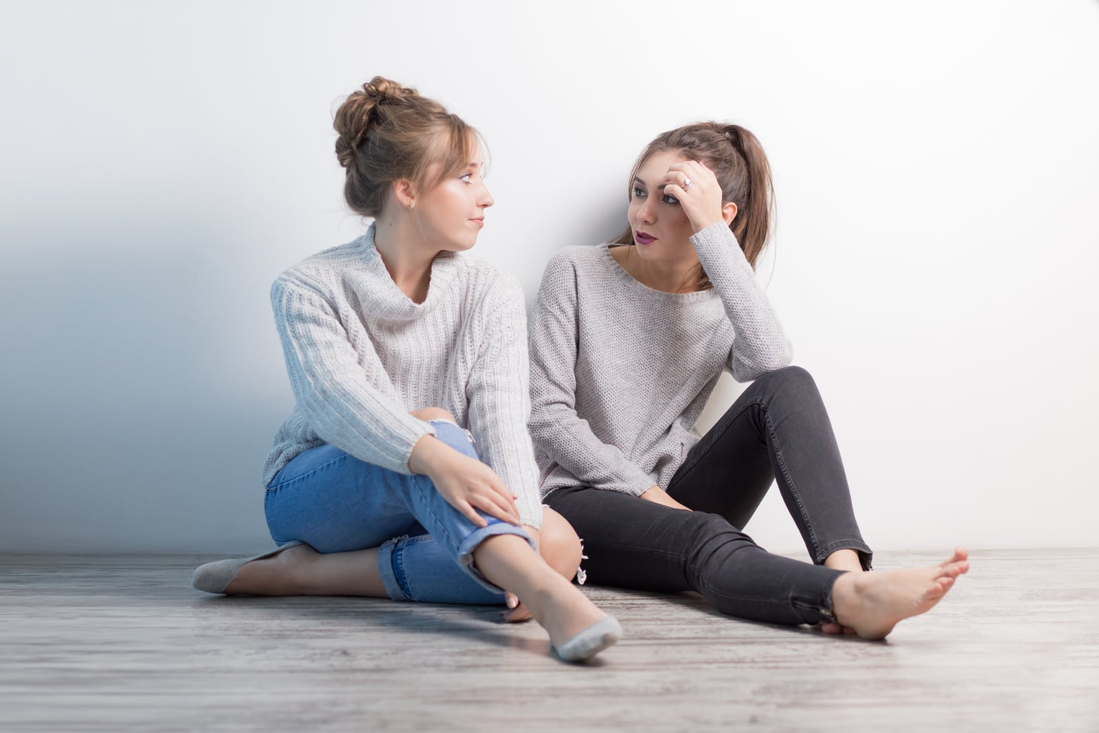 two friends sitting on the floor talking
