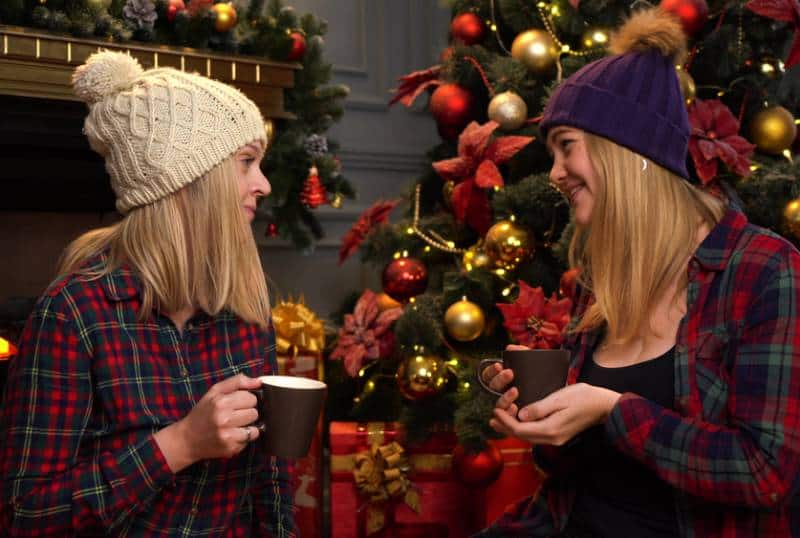 two girls sit under a christmas tree wearing hats