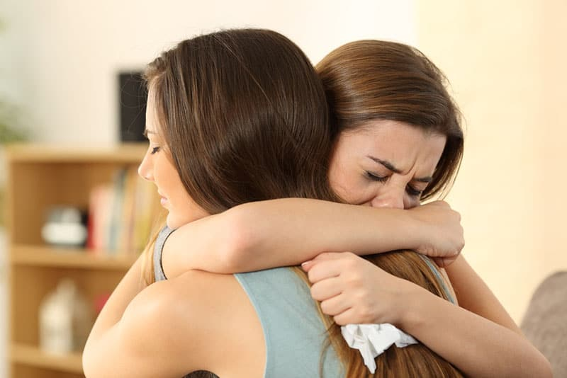 two sad women hugging