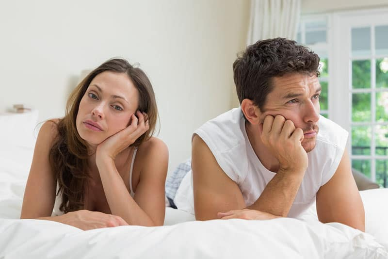 unhappy couple laying on bed