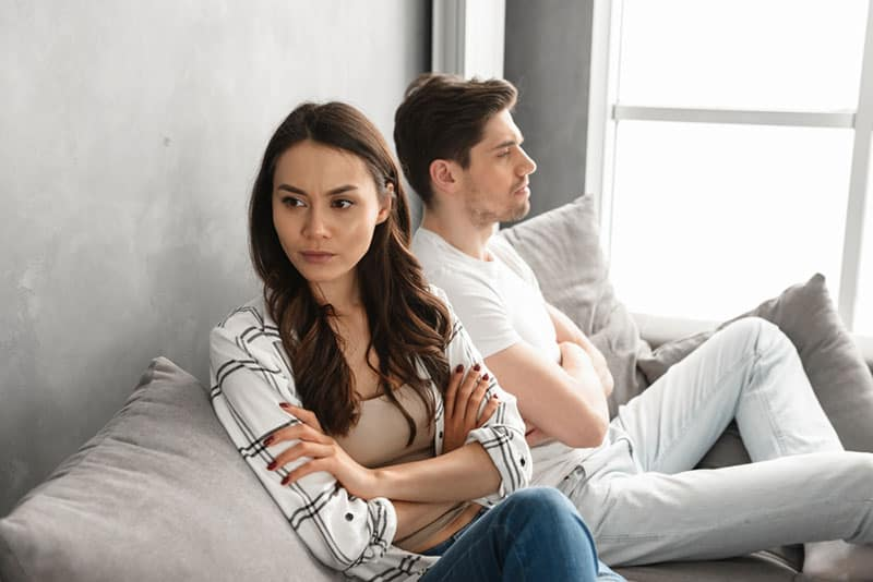unhappy couple sitting on the couch