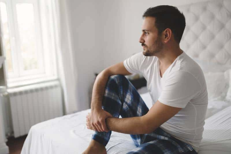 unhappy man in pajamas on bed