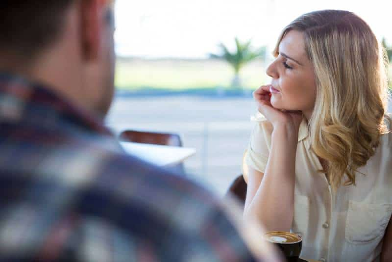 upset woman looking away while sitting with man