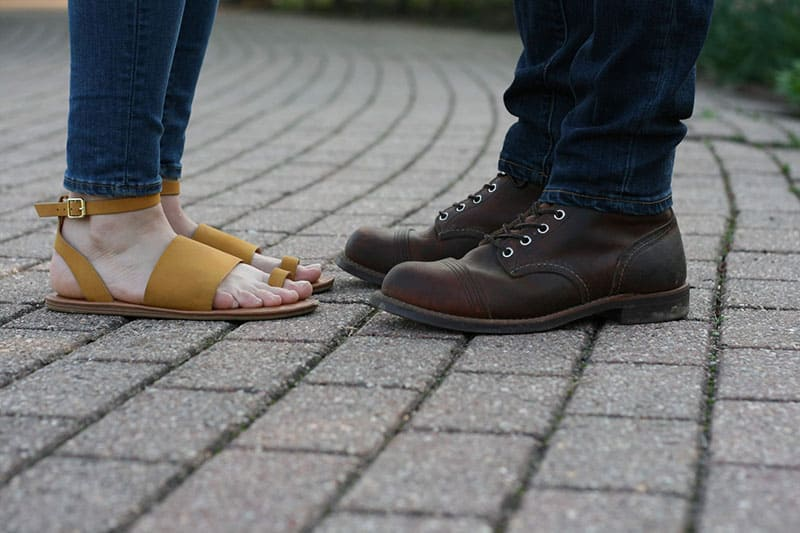 woman and man standing in boots and sandals