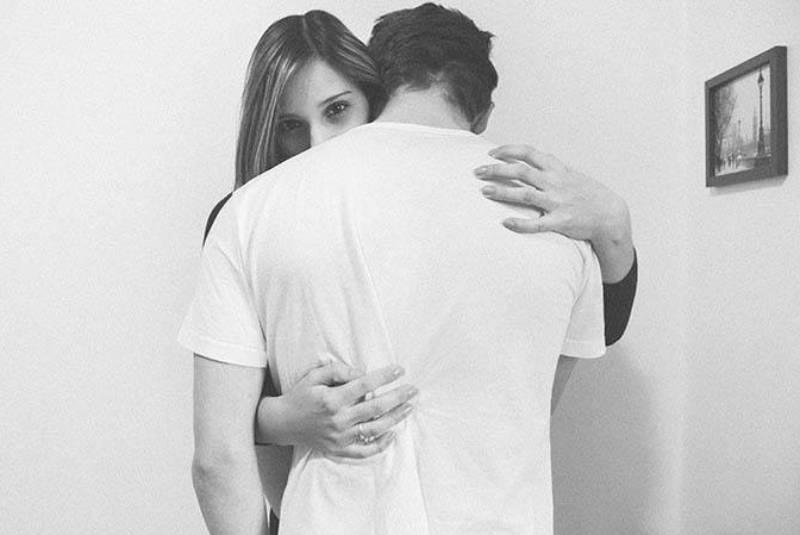 woman hugging man at home