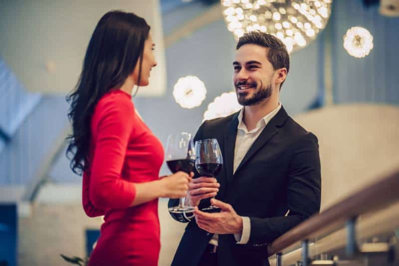 woman in red dress and handsome man in suit having conversation with glass of wine