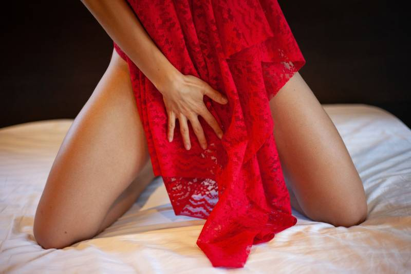 woman in red lace dress lying on bed