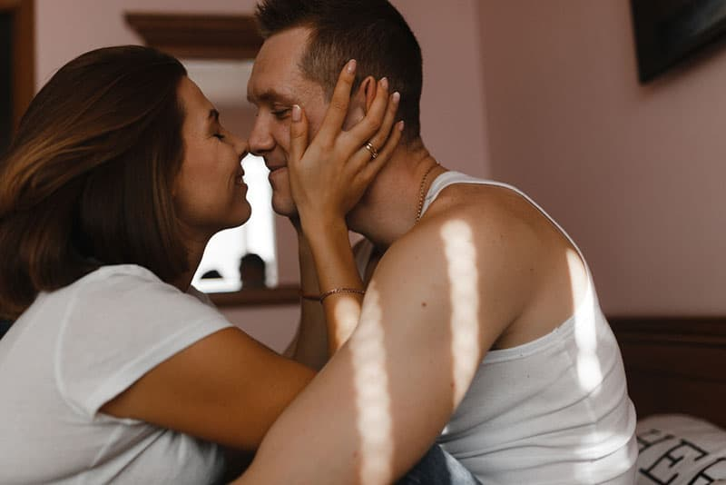 woman kissing a man on bed
