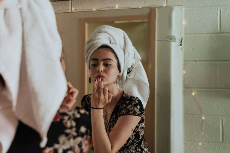woman putting makeup in front of mirror
