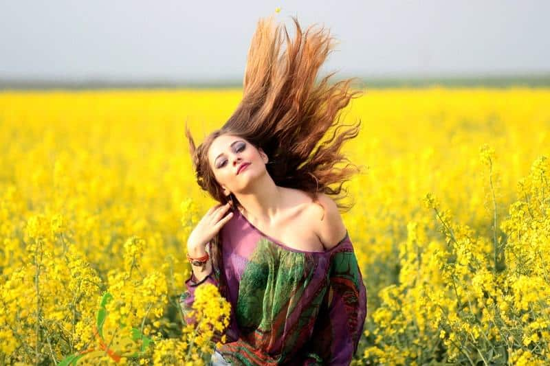 woman standing on yellow flowers field