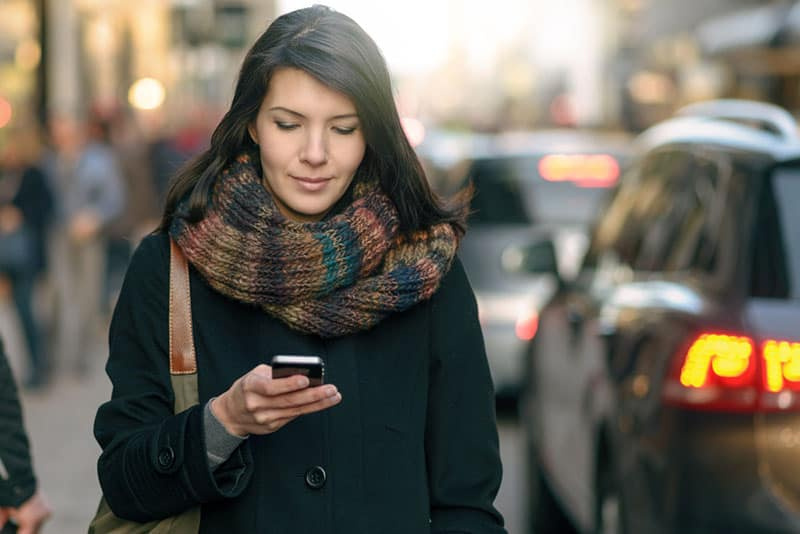 woman wearing jacket and brown scarf typing on her phone outside