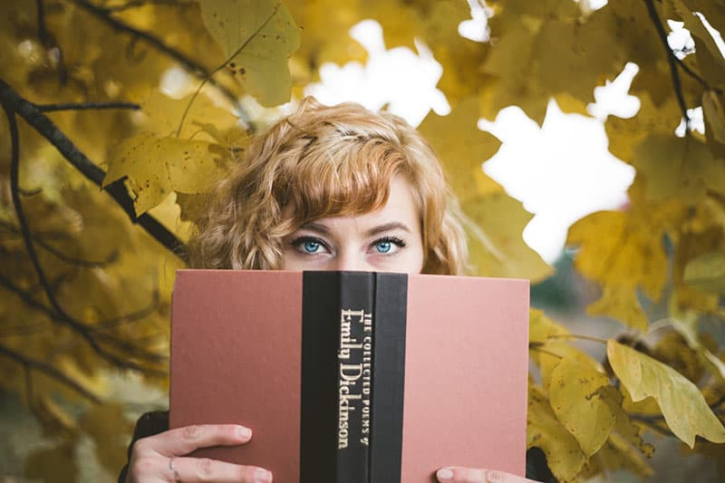 woman with blue eyes holding a book