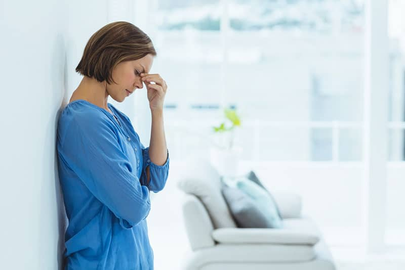 worried woman standing by the wall