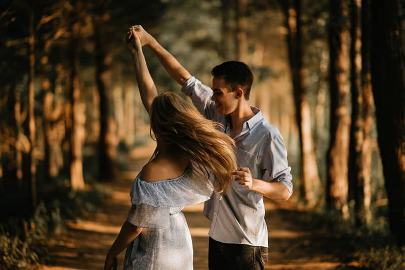 young couple dancing in the wood