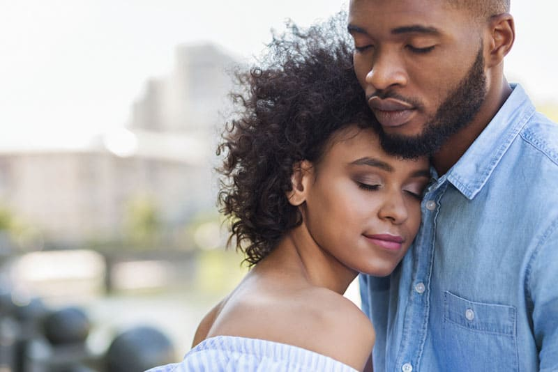 young couple hugging with closed eyes