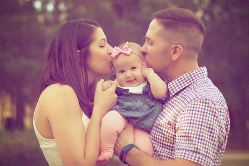 young parents kissing their baby girl