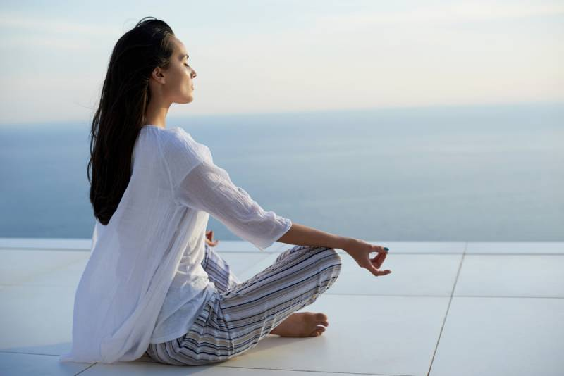 young women practice yoga meditation on sunset with ocean view in background