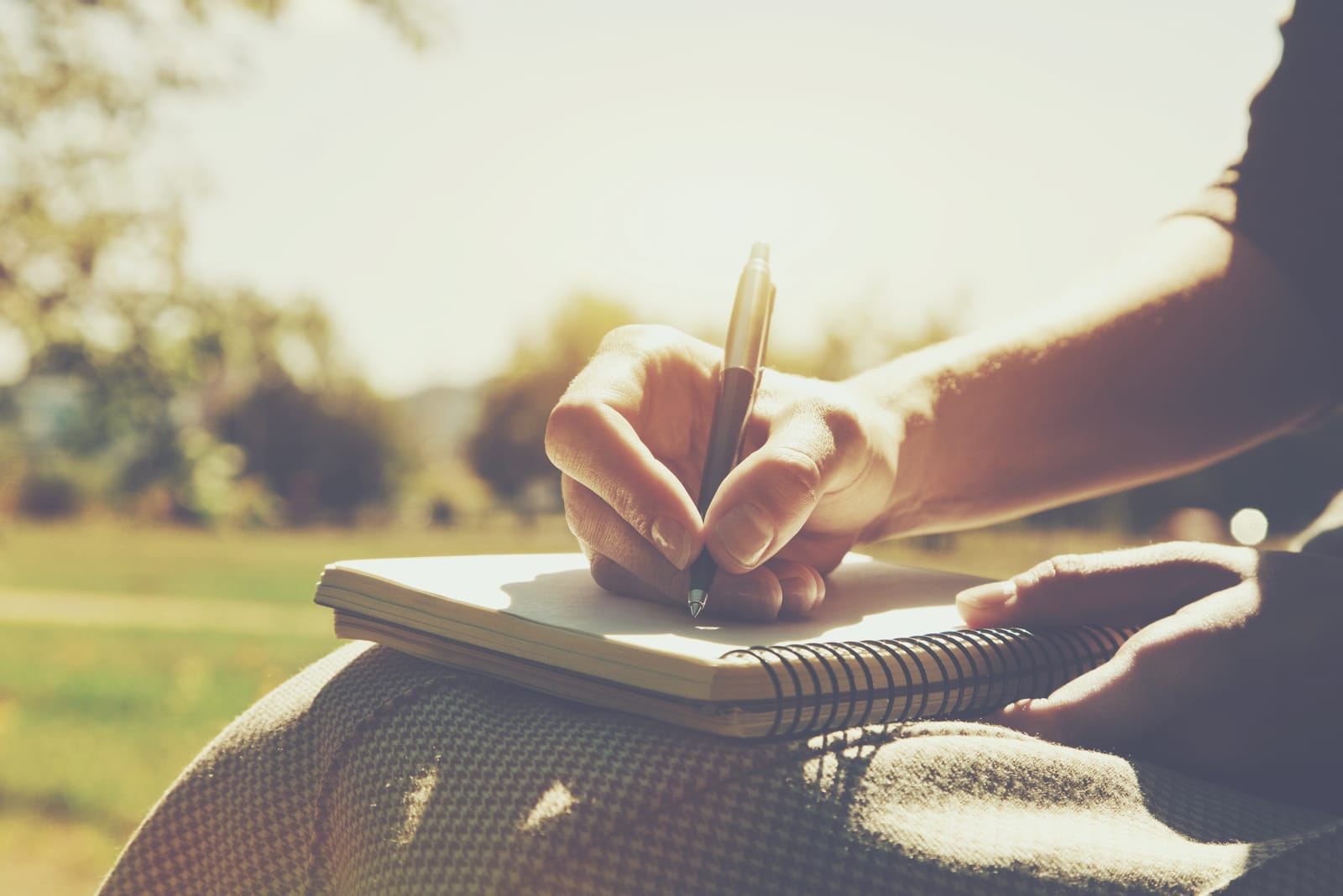 a woman is sitting in the park and writing something in a notebook