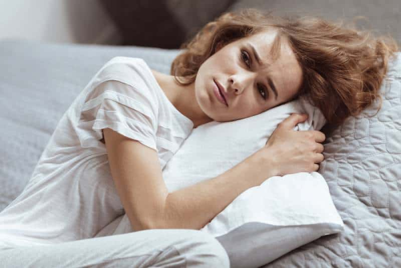 Worried woman lying on a pillow thinking about something depressing at home.
