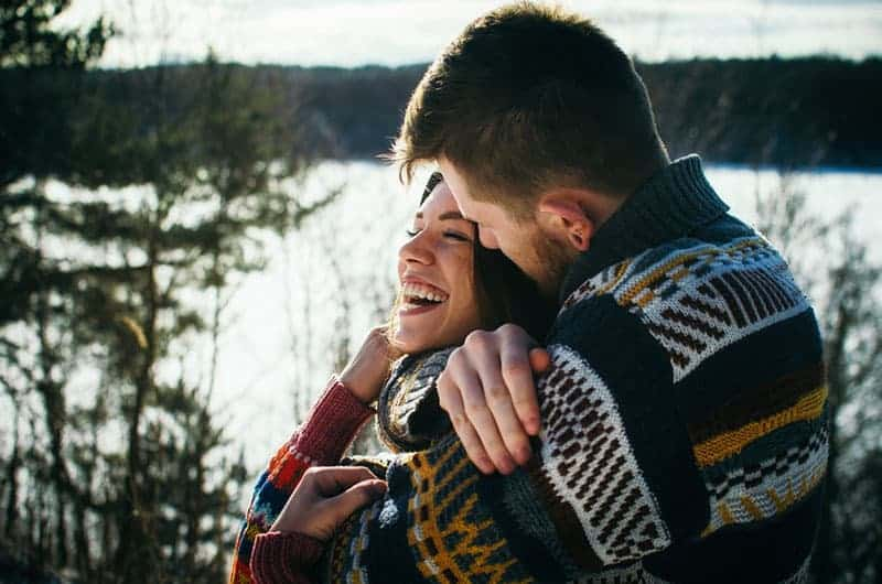 Young man in a sweater hugs a girl from behind