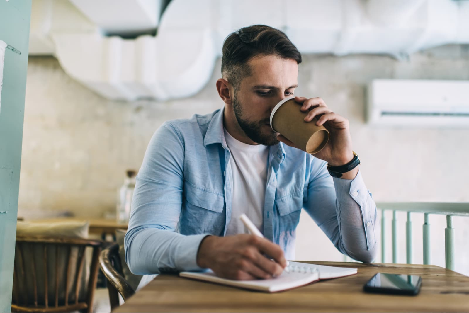 a man sits drinking coffee and writing