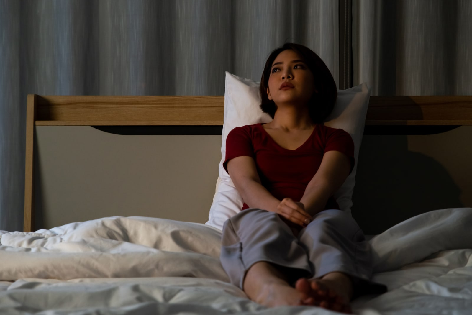 a sad Asian girl sits in bed and thinks