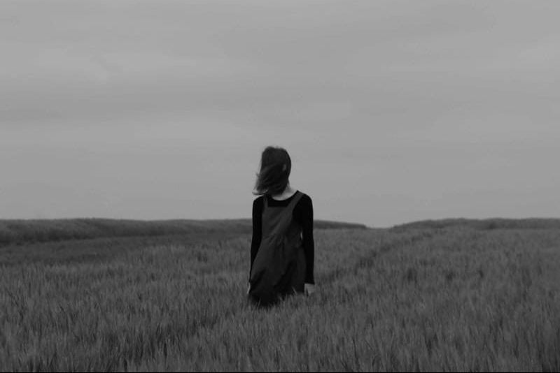 a woman in a black dress at dusk stands in a field of wheat