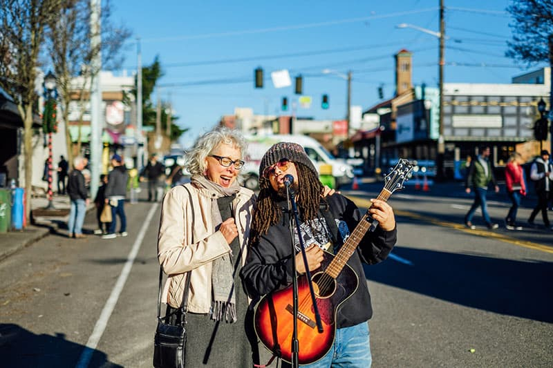 an old woman singing with guy on the street