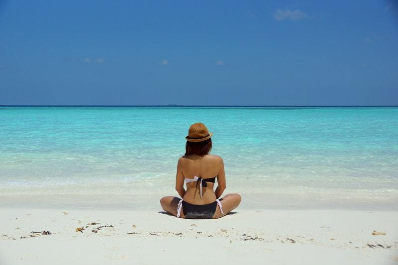back view of woman sitting on the beach