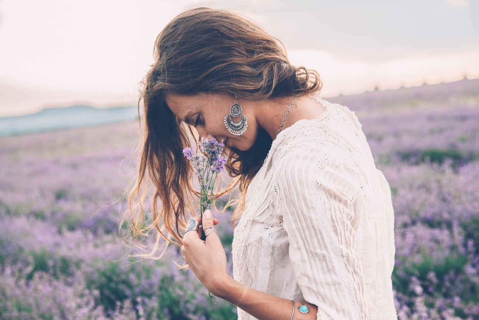 beautiful woman standing on flower field smelling flowers