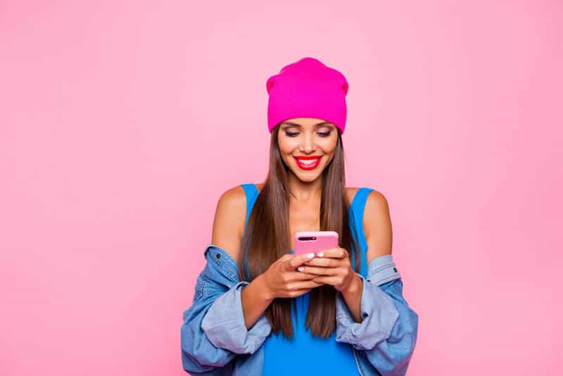 beautiful woman typing on her pink phone with pink background