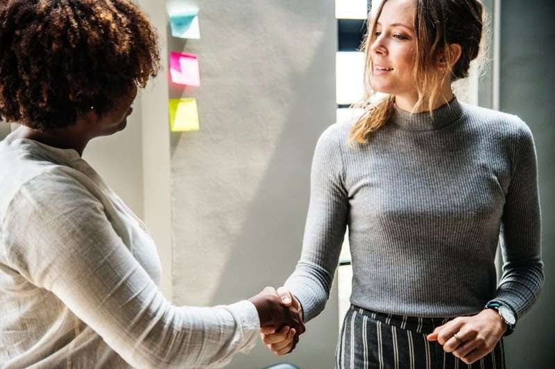 black and white women in the office shake hands