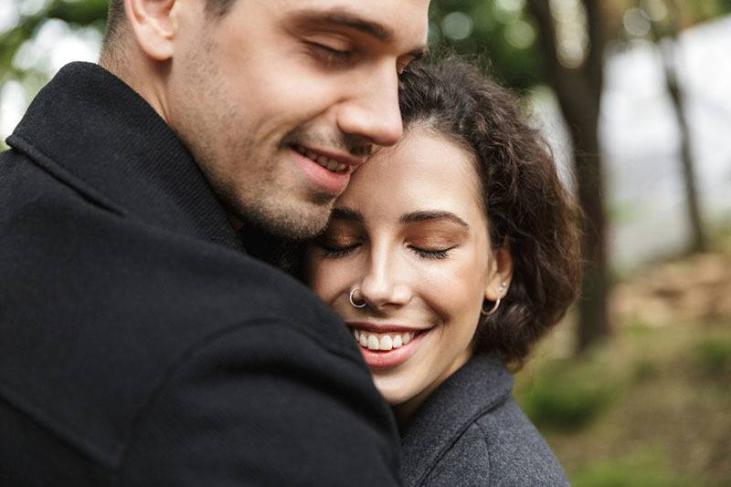 close up of cute couple hugging outside